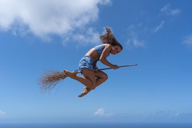空の背景に魔女のふりをしてほうきの若い女性