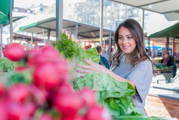 市場に出ている若い女性。いくつかの野菜を拾う幸せな若いブルネット。緑の葉野菜を選ぶ美しい若い女性の肖像