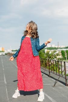 家の屋根の上の若い女性