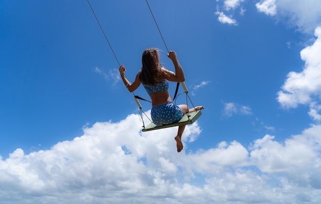 Молодая женщина на качелях веревки с предпосылкой голубого неба. понятие свободы и счастья. фото высокого качества