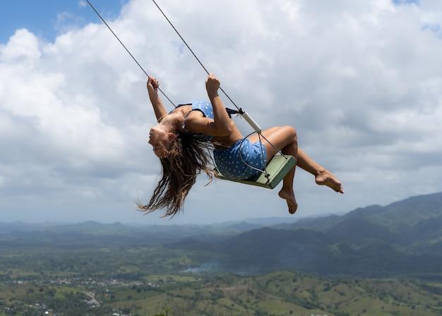 Молодая женщина на качелях веревки с предпосылкой неба и гор. понятие свободы и счастья.
