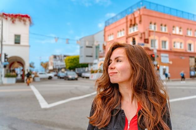 ベニスビーチと有名な碑文ロサンゼルスの青い空と通りの若い女性