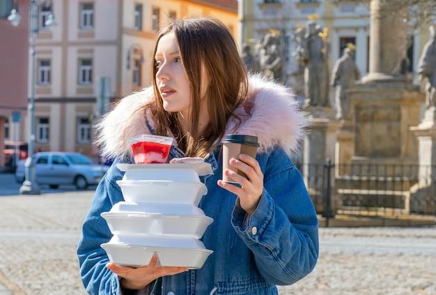 コートを着た通りの若い女性がランチボックスと配達でコーヒーと食べ物を奪う