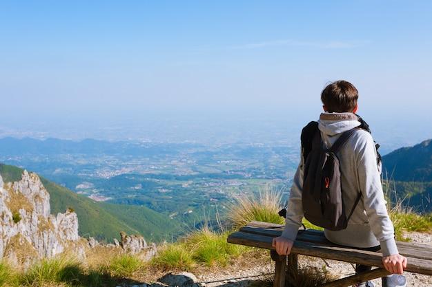 Молодая женщина на вершине горы, глядя на горизонт. панорама гор