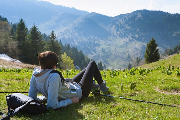 Молодая женщина на вершине горы, сидя на траве. панорама гор