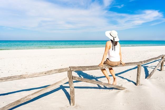 一人で休暇中の若い女性は、青い空の下の白い砂浜の木製の柵に座っている透き通った熱帯の海を賞賛します。夏の旅行を楽しんでいる大きな白い帽子を持つ物思いにふける女の子