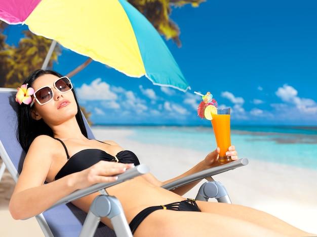 Молодая женщина в отпуске, наслаждаясь на пляже под солнцем