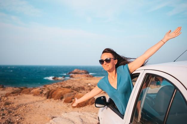車で休暇旅行の若い女性。夏休みと車の旅のコンセプト。家族旅行。