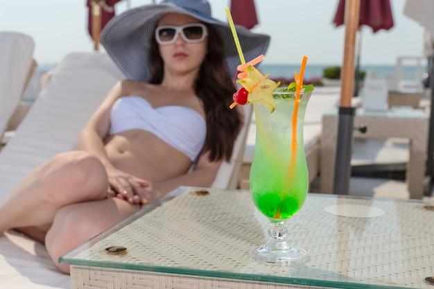 オーシャンフロントラグジュアリービーチリゾートのサンデッキのラウンジチェアでリラックスした白いビキニと大きな日よけ帽を身に着けている休暇中の若い女性、ガラスのテーブルで休んでいる背の高いガラスのトロピカルドリンクに焦点を当てて