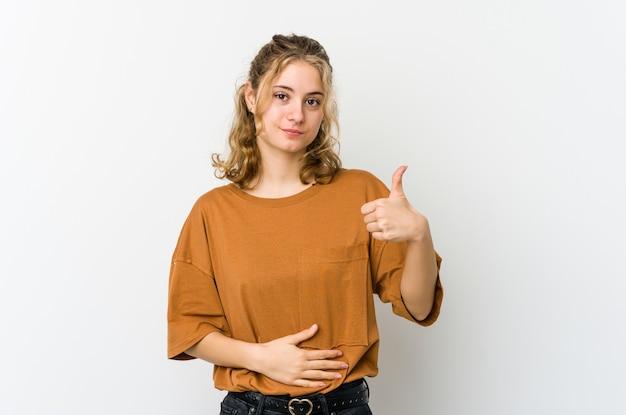 Молодая женщина на белой стене касается животика, нежно улыбается, концепция еды и удовлетворения