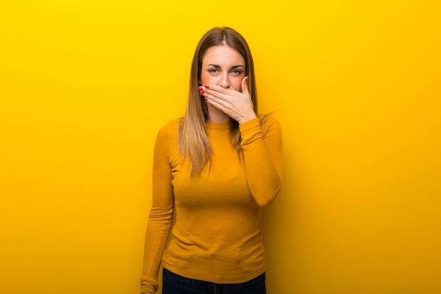 부적절한 내용을 말하기위한 손으로 입을 덮고 노란색 배경에 젊은 여자