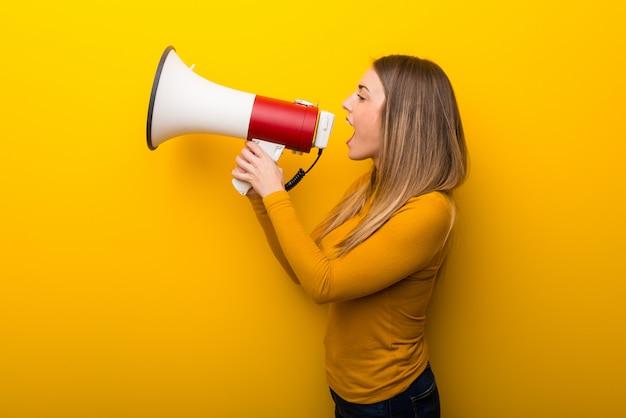 Молодая женщина на желтом фоне кричит через мегафон, чтобы объявить что-то в боковом положении