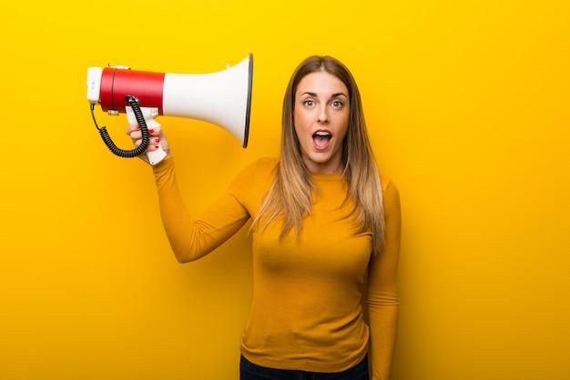 Молодая женщина на желтом фоне, принимая мегафон, который делает много шума