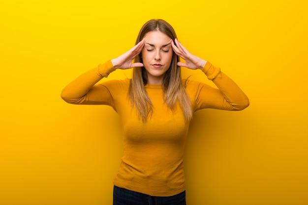 不幸と何かに不満を抱いて黄色の背景に若い女性