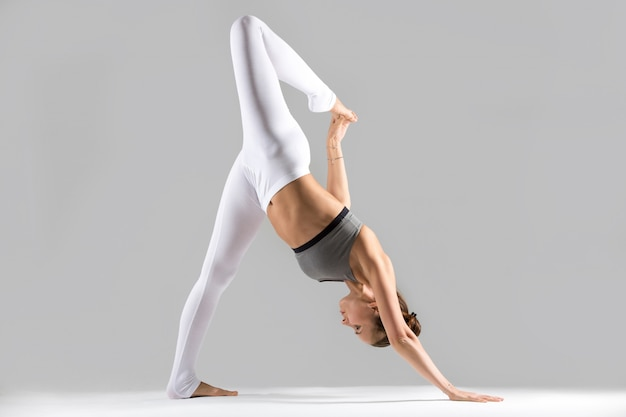 Young woman in one legged downward facing dog pose, studio