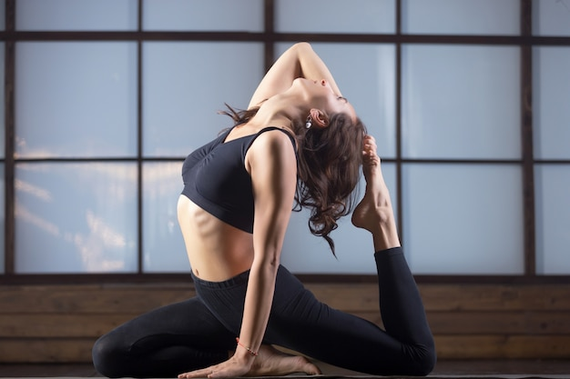 Young woman in one legged king pigeon pose, evening practice