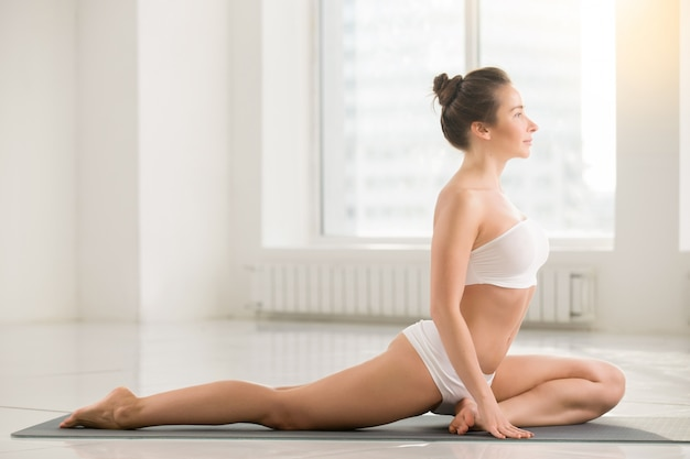 Young woman in one legged king pigeon pose, white background