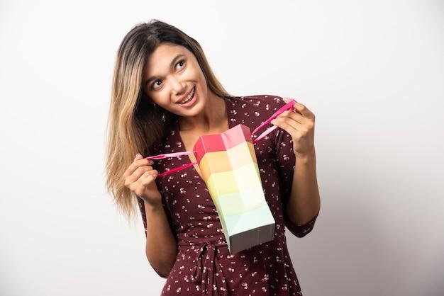 흰 벽에 작은 쇼핑 가방을 여는 젊은 여자.