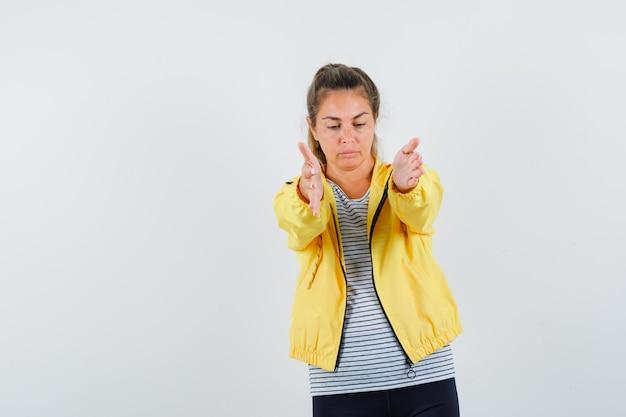 Giovane donna che apre le braccia per abbraccio in t-shirt, giacca e sembra triste, vista frontale.