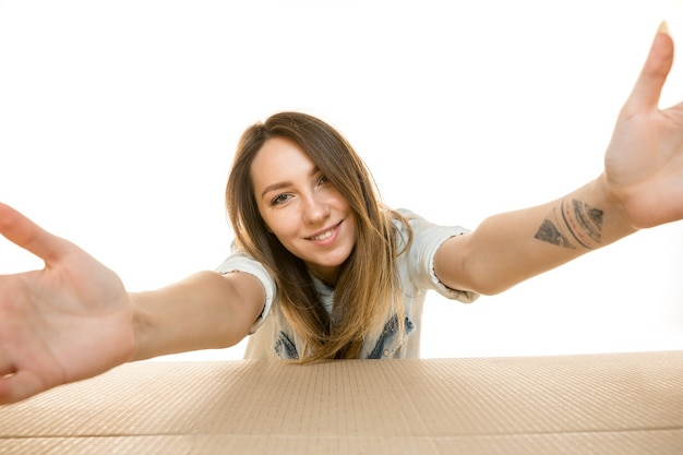 Young woman opening the biggest postal package isolated on white