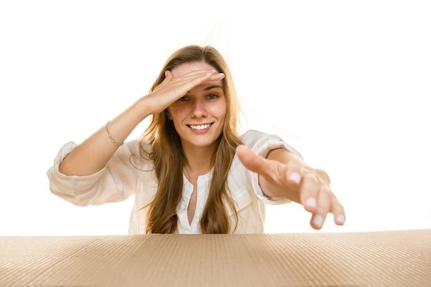 Giovane donna che apre il pacco postale più grande isolato su bianco