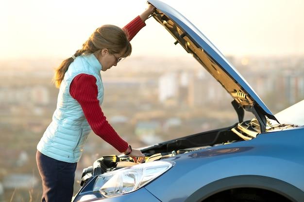 彼女の車に問題を抱えている壊れた車のボンネットを開く若い女性。ポップアップフード付きの自動車の近くの女性ドライバー。