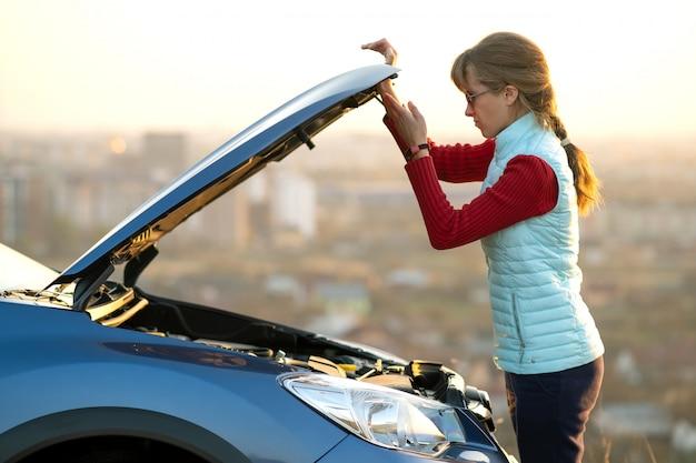 Капот открытия молодой женщины сломленного автомобиля имея проблему с ее кораблем. женщина-водитель возле авто с выскочившим капюшоном.