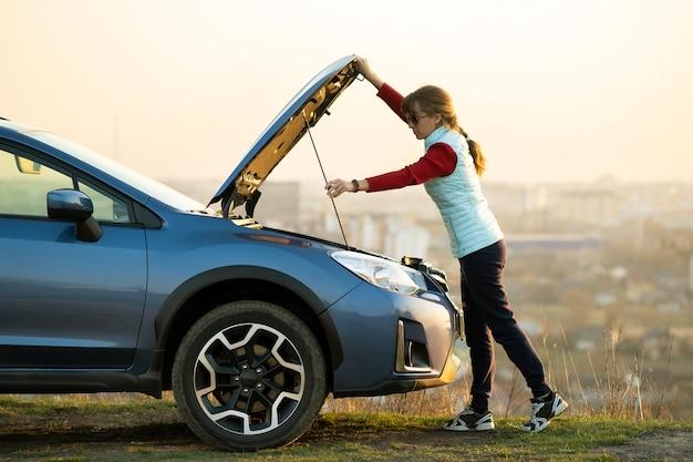 Молодая женщина открывает капот сломанной машины, имея проблемы с ее транспортным средством. женщина-водитель, стоящая возле авто с поднятым капюшоном.