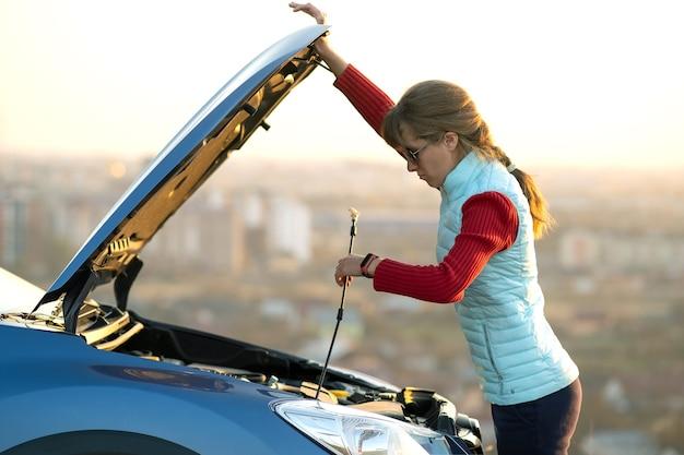 그녀의 차량에 문제가 세분화 자동차의 보닛을 여는 젊은 여자.