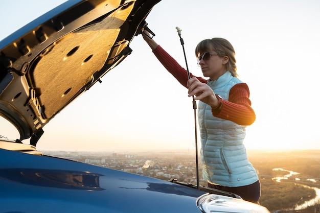 Молодая женщина открывает капот сломанной машины, имея проблемы с ее транспортным средством.