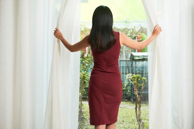 Молодая женщина открывает шторы и смотрит на задний двор в солнечный день