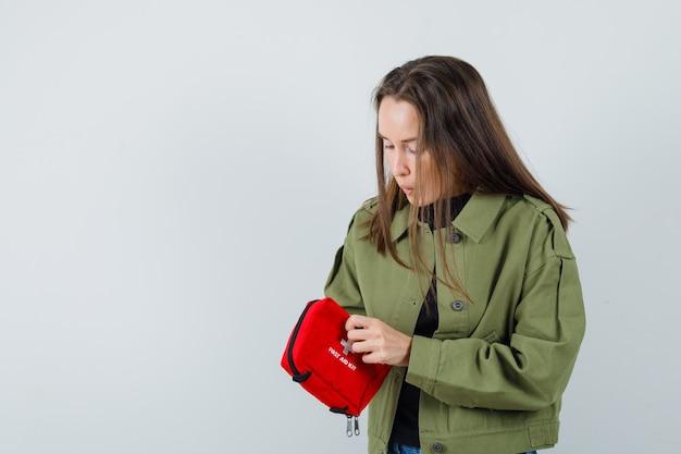 緑のジャケットの正面図で救急箱を開く若い女性。
