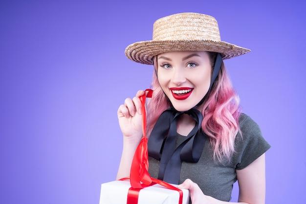 빨간 리본으로 장식 된 그녀의 선물을 여는 젊은 여자