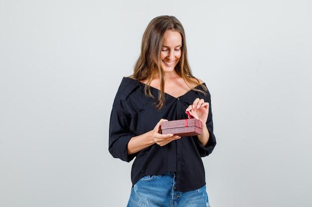 シャツ、ショートパンツでプレゼントボックスを開けて陽気に見える若い女性。正面図。