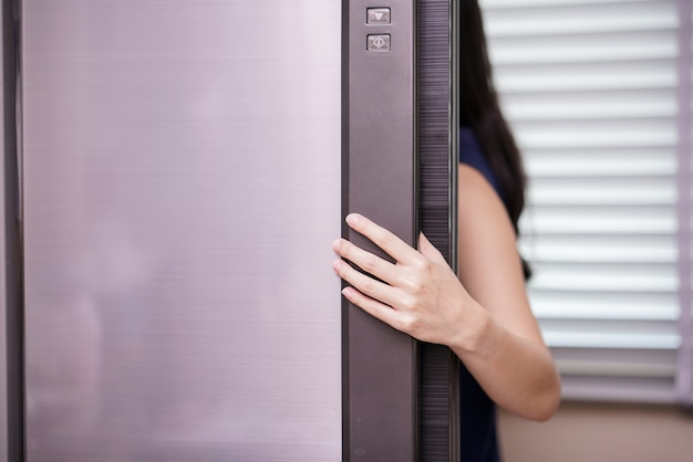 Young woman opening refrigerator, closeup
