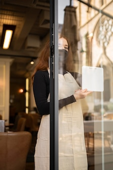 Young woman opening restaurant