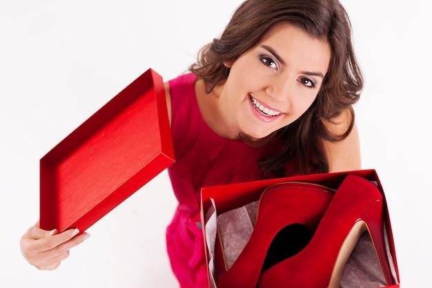 Giovane donna che apre una scatola di scarpe