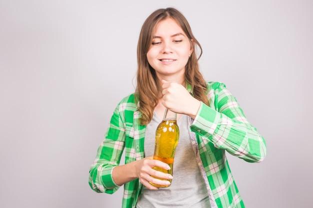 젊은 여자는 맥주 한 병을 엽니 다. 나쁜 습관과 알코올 중독의 개념.