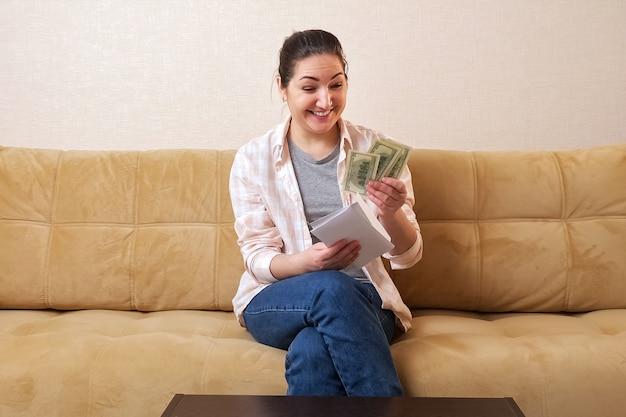 若い女性はソファに請求書とドルで封筒を開きます