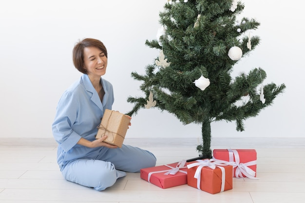 Молодая женщина открывает подарки под рождественской елкой, концепция рождества и нового года