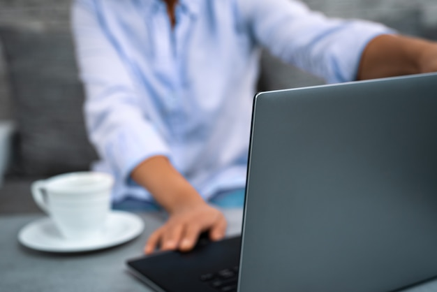 The young woman opens the lid of a laptop to work remotely from home.