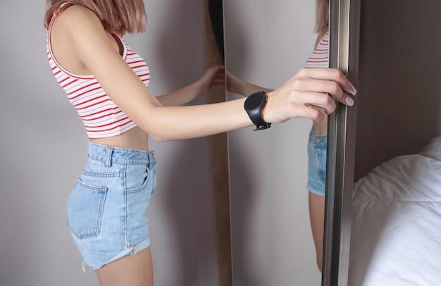 Молодая женщина открывает дверь шкафа дома.
