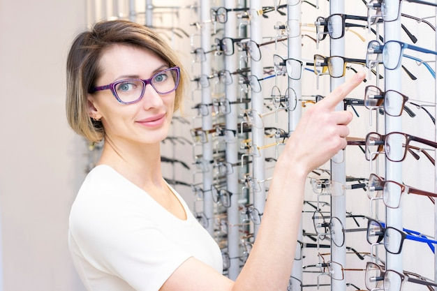 Young woman in optic store choosing new glasses with optician. glasses in the store of optics. a woman chooses glasses. emotions. ophthalmology.