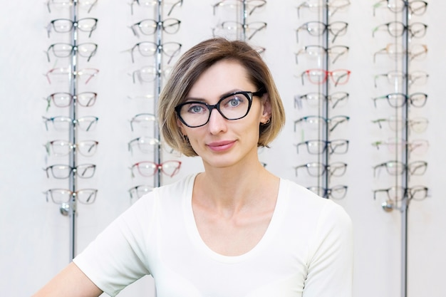 Young woman in optic store choosing new glasses with optician. glasses in the store of optics