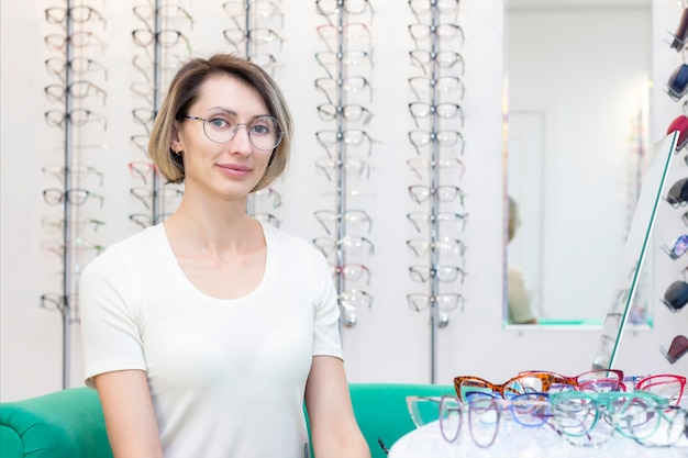 Young woman in optic store choosing new glasses with optician