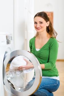 젊은 여성이나 가정부는 집에서 세탁의 날을 보내고, 그녀는 세탁기 또는 건조기에서 꺼냅니다.