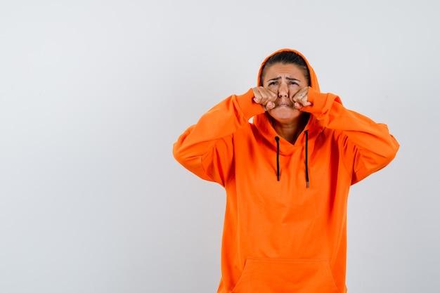 Giovane donna in felpa con cappuccio arancione che stringe i pugni e sembra triste