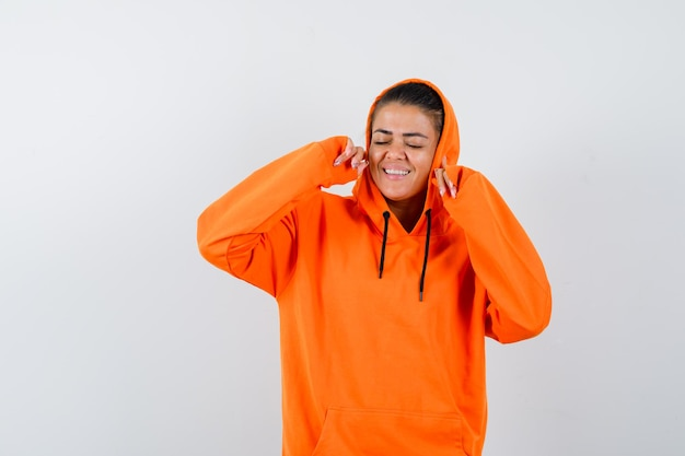 Young woman in orange hoodie clenching fists