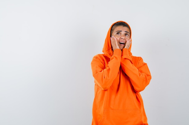 Giovane donna in felpa con cappuccio arancione che si tiene per mano vicino alla bocca mentre chiama qualcuno e sembra concentrata