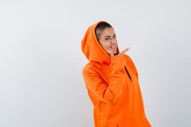 Giovane donna in felpa con cappuccio arancione che punta a destra con il dito indice e sembra felice